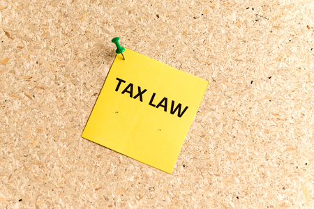tax law: tax law word typed on a paper and pinned to a cork notice board Stock Photo