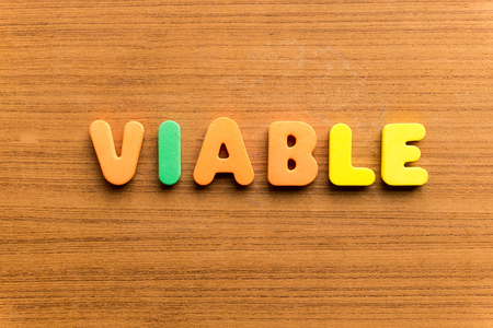 feasible: viable  colorful word on the wooden background