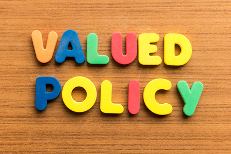 valued: valued policy  colorful word on the wooden background