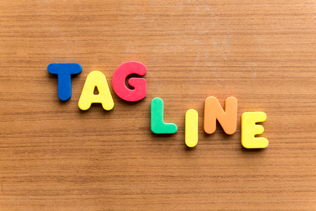 tagline  colorful word on the wooden background Standard-Bild