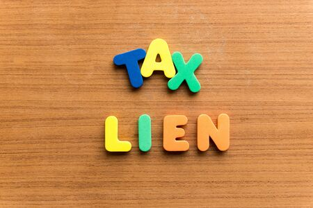 tax lien  colorful word on the wooden background