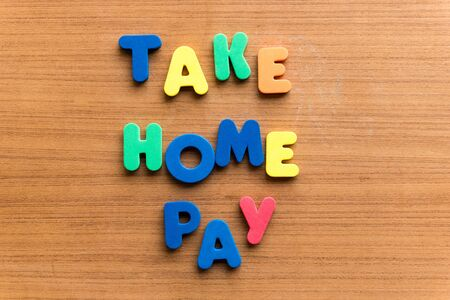 net income: take home pay  colorful word on the wooden background Stock Photo