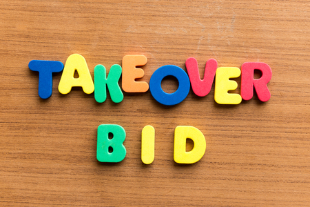 takeover: takeover bid colorful word on the wooden background