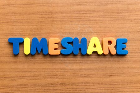 timeshare: Timeshare colorful word on the wooden background