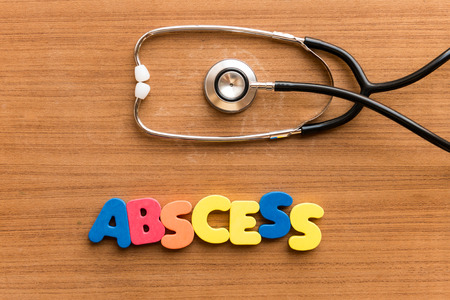 abscess: abscess  colorful word on the wooden background with stethoscope