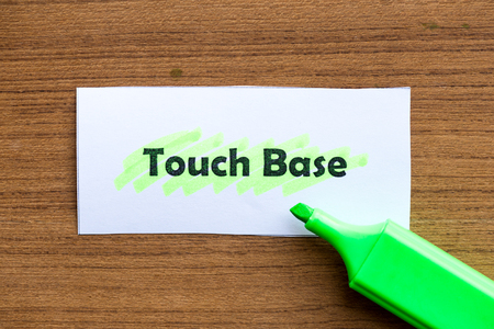 touch base: touch base word highlighted on the white paper Stock Photo