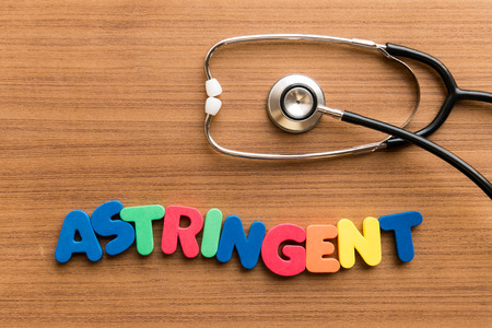 astringent: Astringent  colorful word on the wooden background with stethoscope