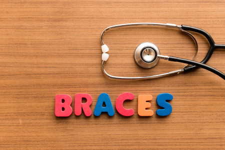 braces  colorful word on the wooden background with stethoscope Stock Photo