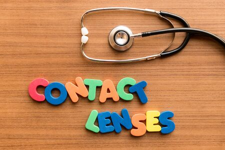 lentes de contacto: contact lenses colorful word on the wooden background with stethoscope