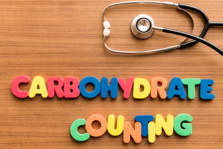 carbohydrate counting colorful word on the wooden background with stethoscope Standard-Bild