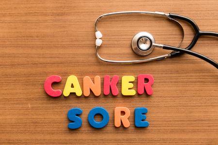 lesion: canker sore colorful word on the wooden background with stethoscope Stock Photo