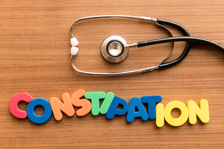 crick: constipation colorful word on the wooden background with stethoscope Stock Photo