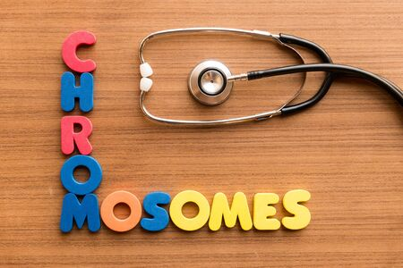 chromosomes: chromosomes colorful word on the wooden background with stethoscope