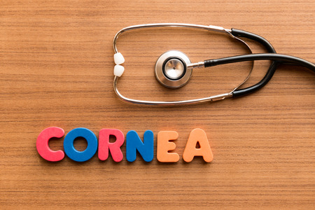cornea: cornea colorful word on the wooden background with stethoscope