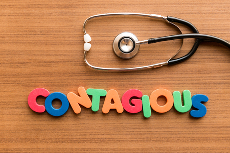 transmissible: contagious colorful word on the wooden background with stethoscope Stock Photo