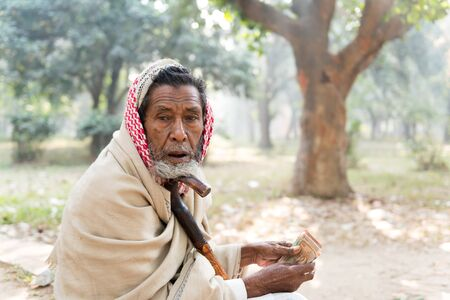 poverty relief: Dhaka, Bangladesh - January 02, 2016: Beggar counting money sitting on the road - closeup on hands Editorial