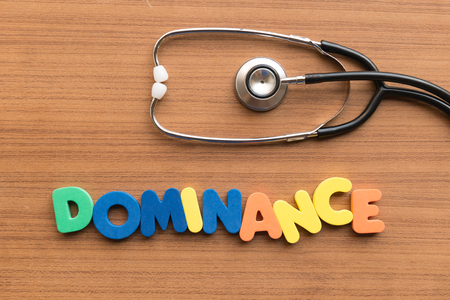 dominance: dominance colorful word on the wooden background