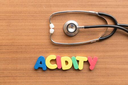acidity: acidity colorful word on the wooden background Stock Photo