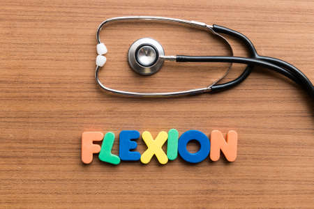 flexion: flexion colorful word on the wooden background with stethoscope Stock Photo