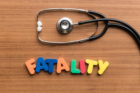 fatality: fatality colorful word on the wooden background with stethoscope