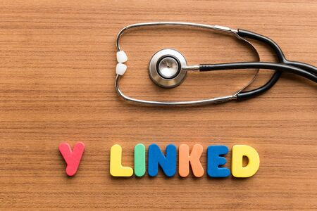 linked: y linked colorful word on the wooden background with stethoscope Stock Photo