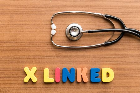 linked: x linked colorful word on the wooden background with stethoscope