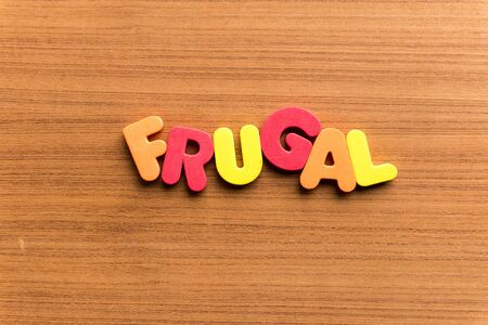 frugal: frugal colorful word on the wooden background
