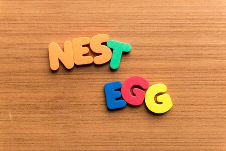 nest egg: nest egg colorful word on the wooden background