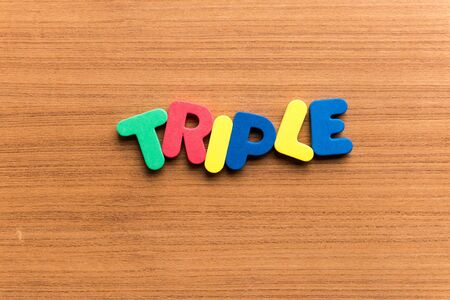 triple: triple colorful word on the wooden background