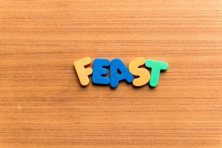 feast: feast colorful word on the wooden background Stock Photo