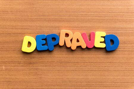 depraved colorful word on the wooden background Stock Photo