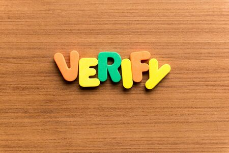 verify: verify colorful word on the wooden background Stock Photo