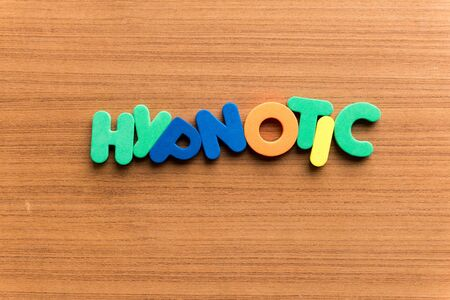 hypnotic: hypnotic colorful word on the wooden background