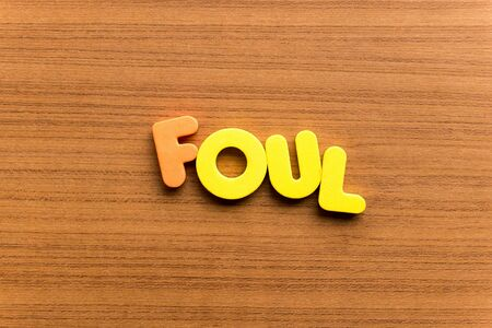 foul: foul colorful word on the wooden background Stock Photo