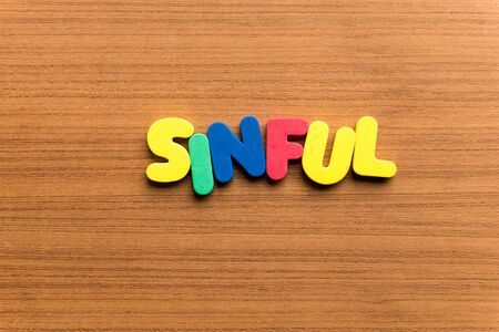sinful: sinful colorful word on the wooden background