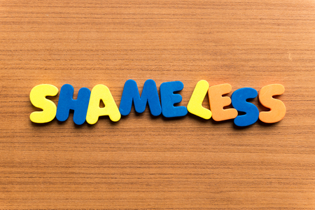 shameless colorful word on the wooden background