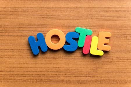 hostile: hostile colorful word on the wooden background