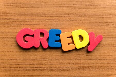 greedy: greedy colorful word on the wooden background