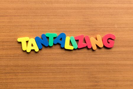 tantalizing colorful word on the wooden background