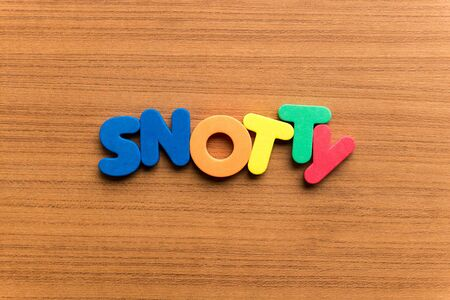 snotty: snotty colorful word on the wooden background