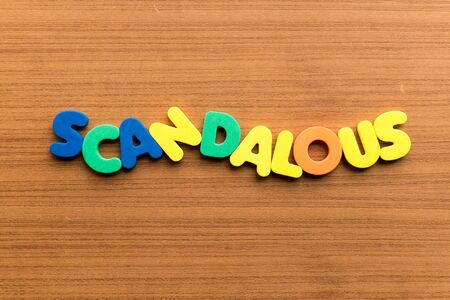 scandalous: scandalous colorful word on the wooden background