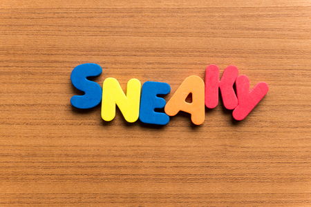 sneaky: sneaky colorful word on the wooden background