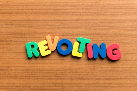 revolting: revolting colorful word on the wooden background Stock Photo