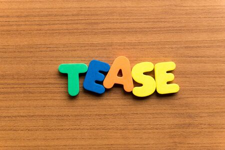 to tease: tease colorful word on the wooden background Stock Photo