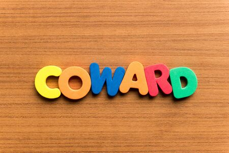 coward: coward colorful word on the wooden background