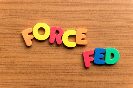are fed: force fed colorful word on the wooden background Stock Photo