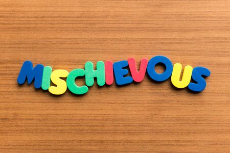 mischievous: mischievous colorful word on the wooden background Stock Photo