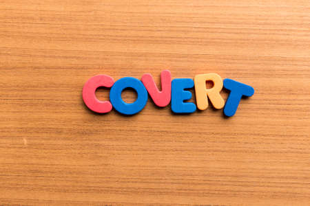 furtive: covert colorful word on the wooden background Stock Photo