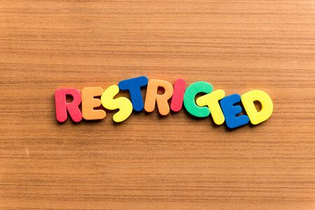 bounded: restricted colorful word on the wooden background Stock Photo