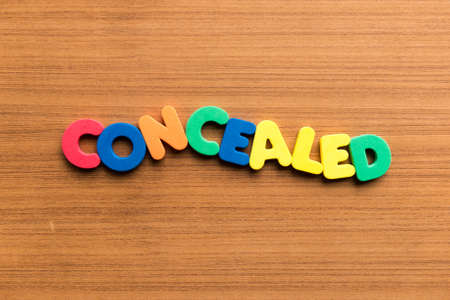 concealed: concealed colorful word on the wooden background